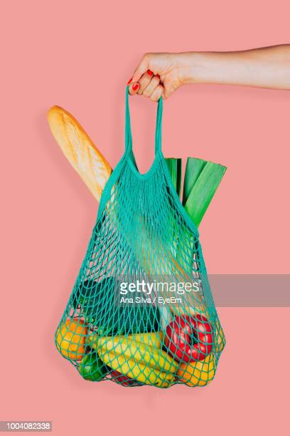 cropped hand of woman holding food in bag against peach background - sac photos et images de collection