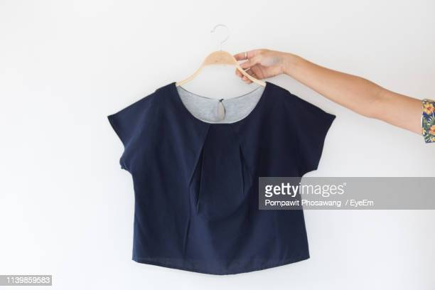 cropped hand of woman holding garment against white background - womenswear stock pictures, royalty-free photos & images