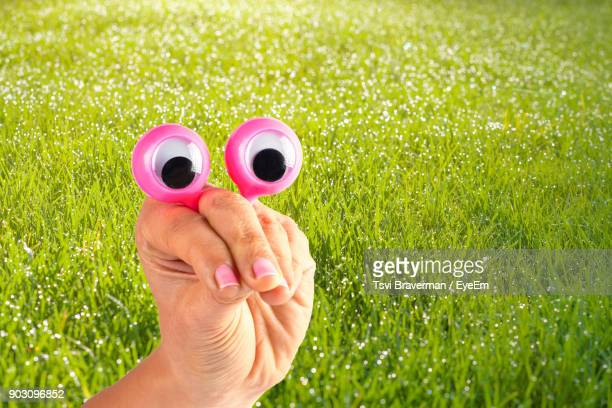 cropped hand of woman holding googly eyes toy over field - googly eyes stock pictures, royalty-free photos & images