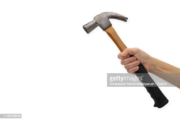 cropped hand of woman holding hammer against white background - hammer stock pictures, royalty-free photos & images
