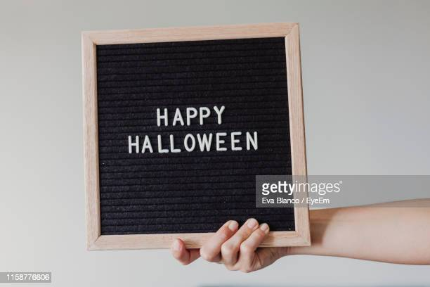 cropped hand of woman holding happy halloween text against white background - capital letter stock pictures, royalty-free photos & images