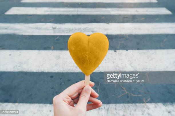 Cropped Hand Of Woman Holding Heart Shape Candy On Road