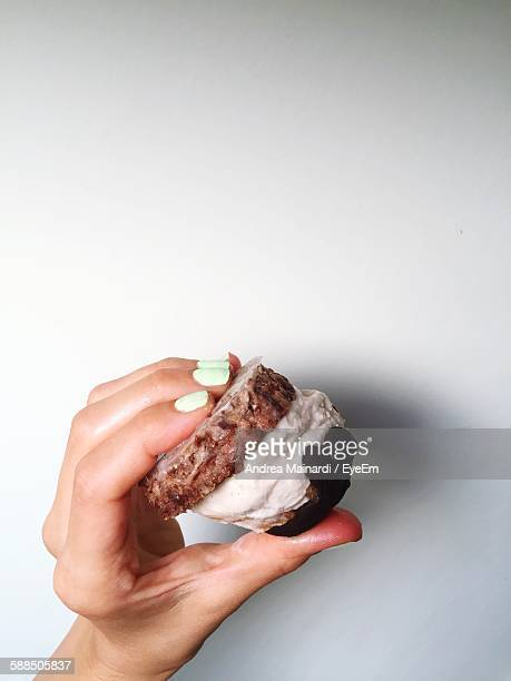 Cropped Hand Of Woman Holding Ice Cream Sandwich Against White Wall