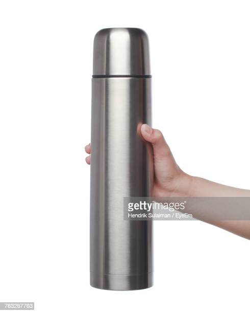 cropped hand of woman holding insulated drink container against white background - flask stock pictures, royalty-free photos & images