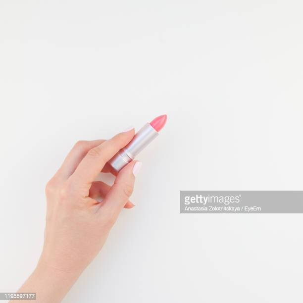 cropped hand of woman holding lipstick against white background - rossetto foto e immagini stock