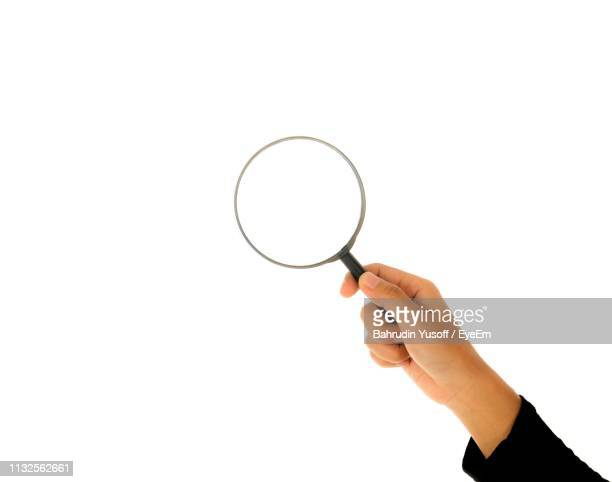 cropped hand of woman holding magnifying glass against white background - magnifying glass stock pictures, royalty-free photos & images