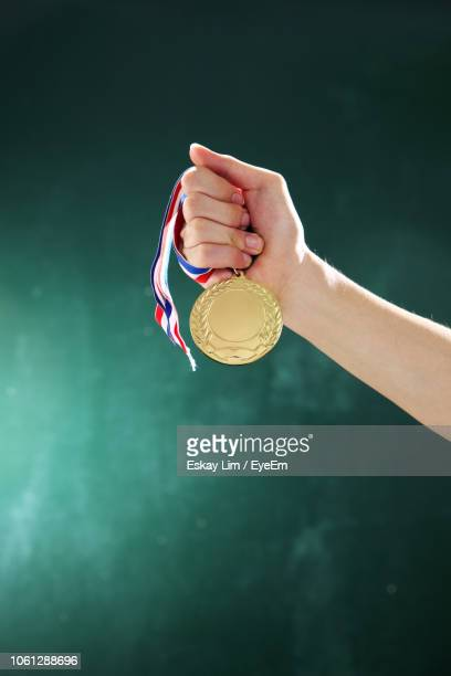 cropped hand of woman holding medal against wall - medal stock pictures, royalty-free photos & images