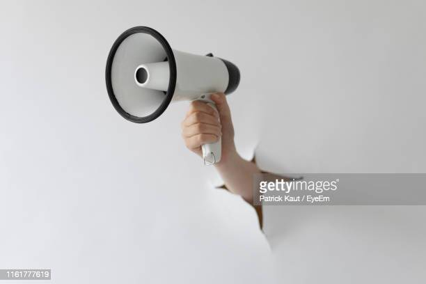 cropped hand of woman holding megaphone through torn paper - megaphone stock pictures, royalty-free photos & images