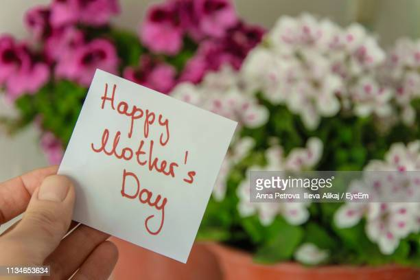 cropped hand of woman holding message by bouquet during mother day - mothers day stock pictures, royalty-free photos & images