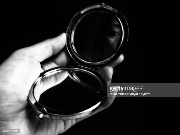 cropped hand of woman holding mirror against black background - hand mirror stock pictures, royalty-free photos & images