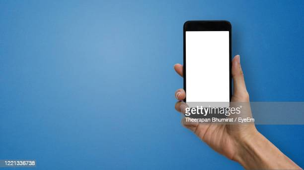 cropped hand of woman holding mobile phone against blue background - woman blue background stock pictures, royalty-free photos & images
