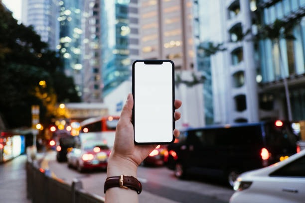 cropped hand of woman holding mobile phone in front of urban skyscrapers in downtown financial district with busy city traffic - human hand stock pictures, royalty-free photos & images