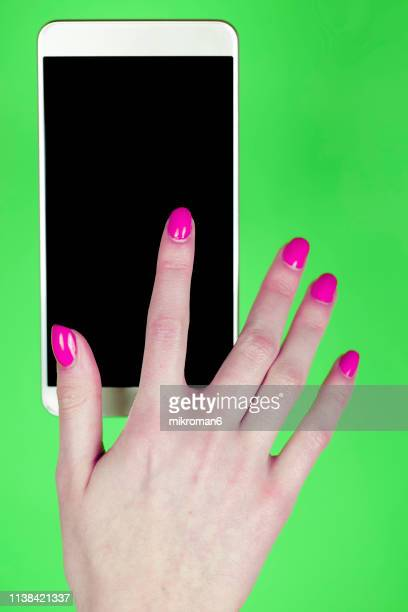 cropped hand of woman holding mobile phone over colored background - pop art stock pictures, royalty-free photos & images
