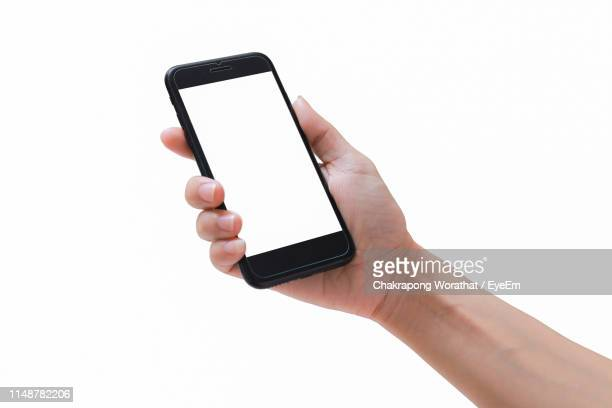 cropped hand of woman holding mobile phone over white background - menselijke hand stockfoto's en -beelden