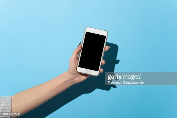 cropped hand of woman holding mobile phone - human hand stock pictures, royalty-free photos & images