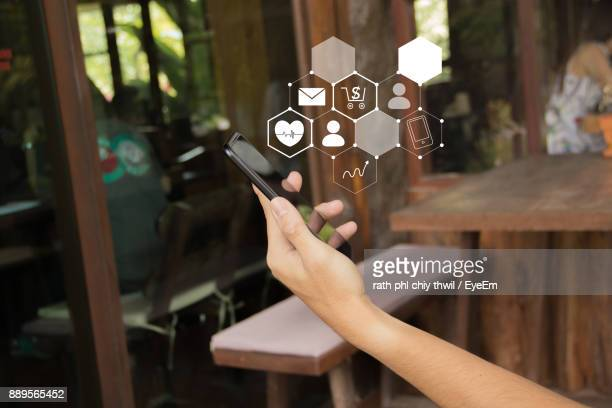 Cropped Hand Of Woman Holding Mobile Phone With Icons