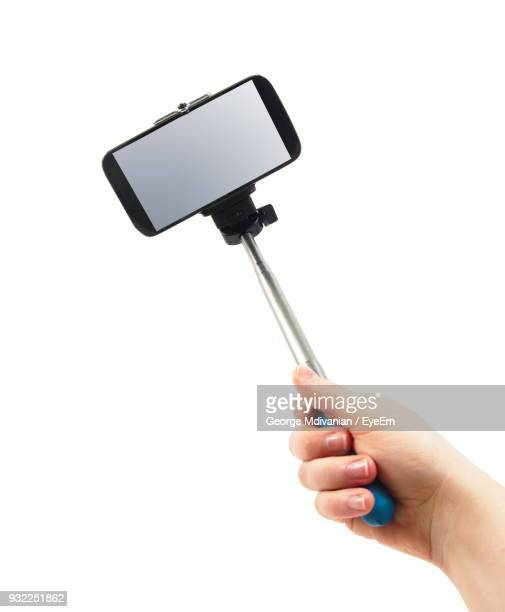Cropped Hand Of Woman Holding Monopod With Smart Phone Against White Background