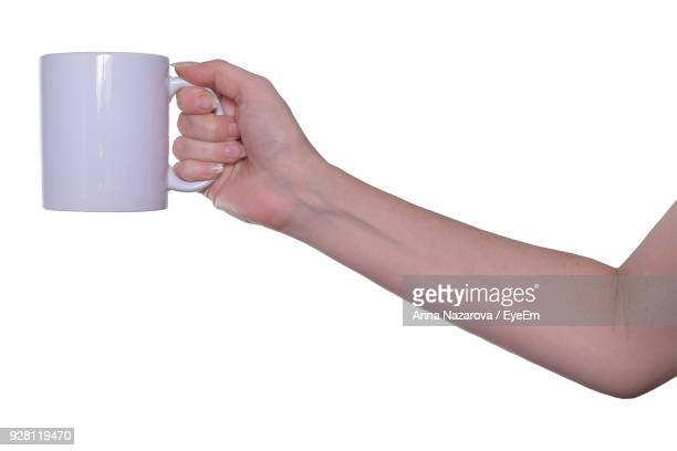 cropped hand of woman holding mug against white background - mug stock pictures, royalty-free photos & images