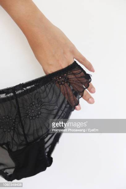cropped hand of woman holding panties against white background - black slip photos et images de collection
