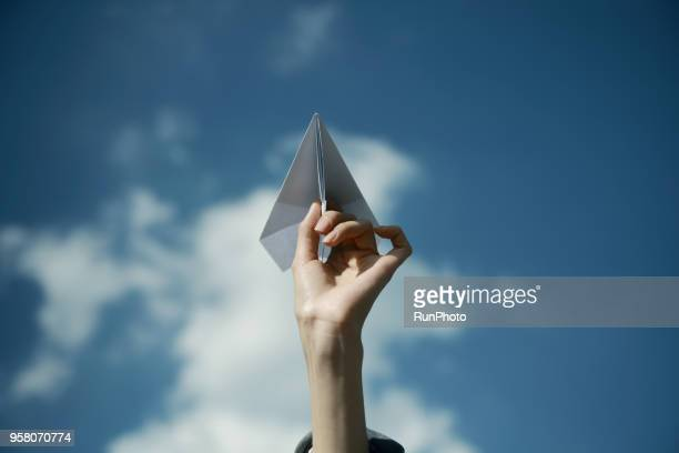 cropped hand of woman holding paper airplane against sky - lanciare foto e immagini stock