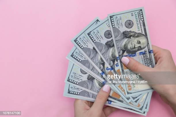 cropped hand of woman holding paper currencies against pink background - dinero fotografías e imágenes de stock