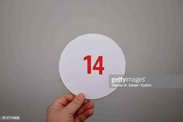 cropped hand of woman holding paper with number over gray background - number 14 stock photos and pictures