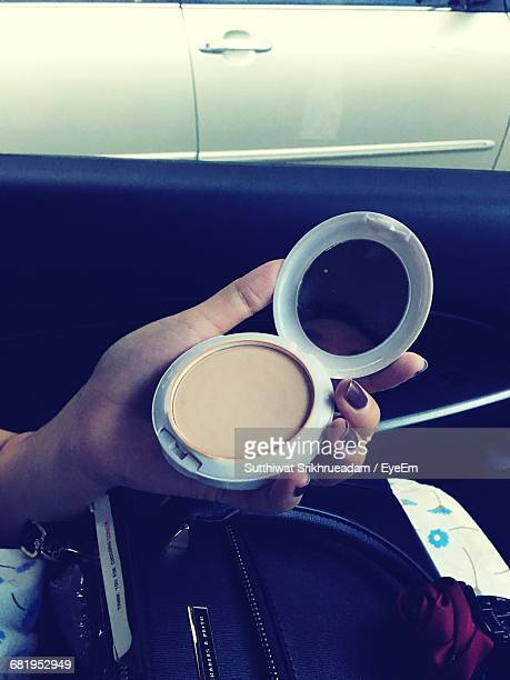 Cropped Hand Of Woman Holding Powder Compact In Car