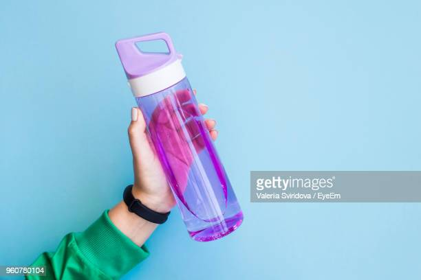 cropped hand of woman holding purple water bottle against blue background - bottle stock pictures, royalty-free photos & images