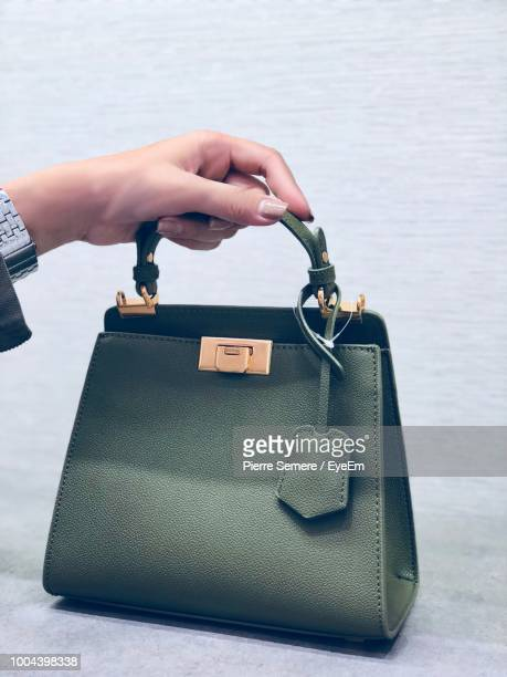 cropped hand of woman holding purse - borsetta da sera foto e immagini stock