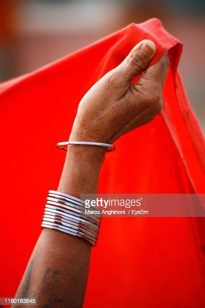 cropped hand of woman holding red scarf - bangle stock pictures, royalty-free photos & images