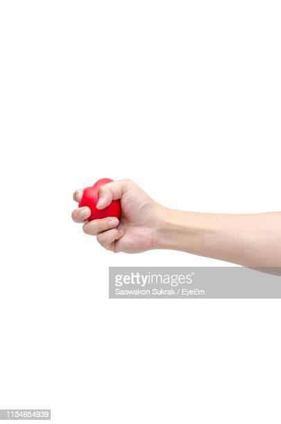 cropped hand of woman holding red stress ball over white background - gripping stock pictures, royalty-free photos & images