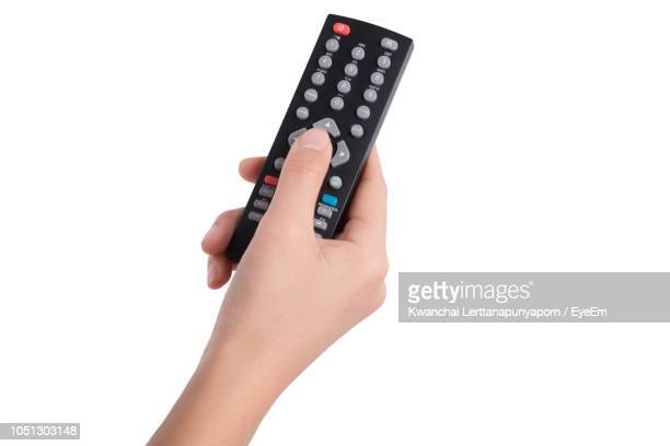cropped hand of woman holding remote control against white background - afstandsbediening stockfoto's en -beelden