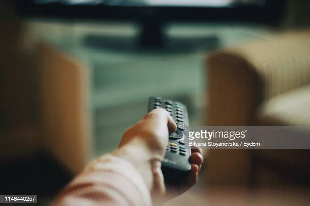 cropped hand of woman holding remote control - remote control stock pictures, royalty-free photos & images