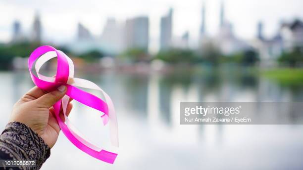 Cropped Hand Of Woman Holding Ribbons Against Lake