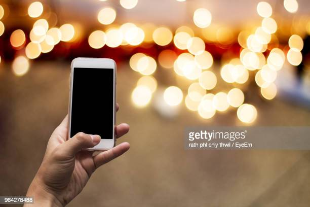 Cropped Hand Of Woman Holding Smart Phone Against Illuminated Lights