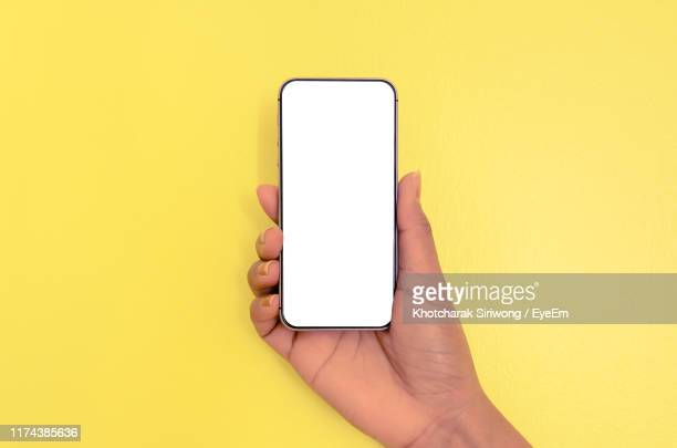 cropped hand of woman holding smart phone over yellow background - menselijke hand stockfoto's en -beelden