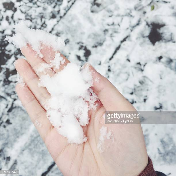 Cropped Hand Of Woman Holding Snow On Palm During Winter