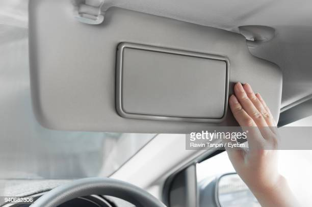 Cropped Hand Of Woman Holding Sun Visor In Car bba46afaf2e