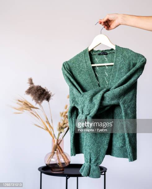 cropped hand of woman holding sweater against white background - green coat stock pictures, royalty-free photos & images
