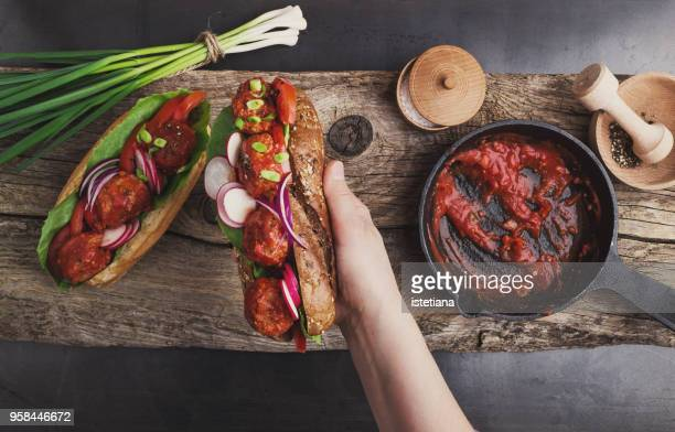 cropped hand of woman holding vegan meatball sandwish - marinara stock photos and pictures