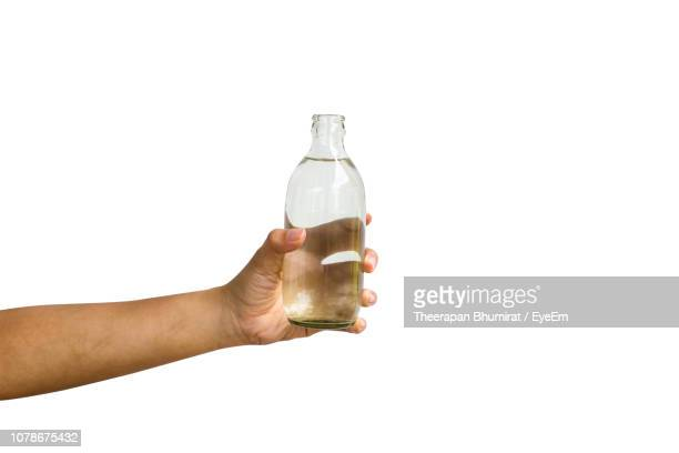 cropped hand of woman holding water in bottle against white background - human hand stock pictures, royalty-free photos & images