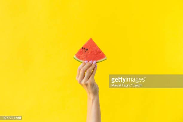 cropped hand of woman holding watermelon against yellow background - watermelon stock pictures, royalty-free photos & images