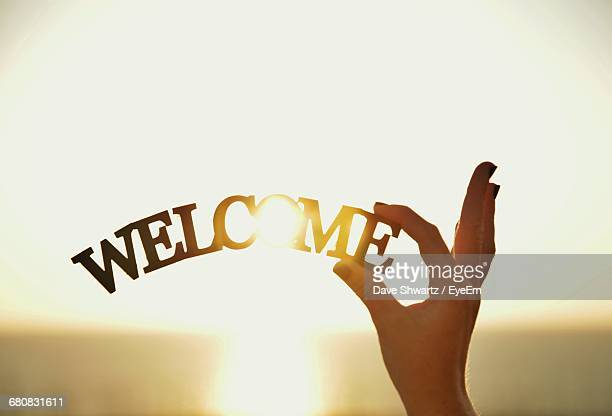 cropped hand of woman holding welcome sign - greeting foto e immagini stock