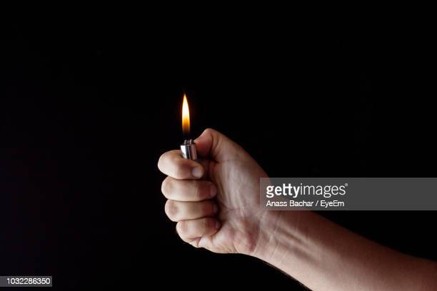 cropped hand of woman igniting cigarette lighter against black background - cigarette lighter stock pictures, royalty-free photos & images