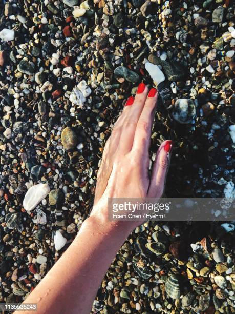 cropped hand of woman in sea - red nail polish stock pictures, royalty-free photos & images