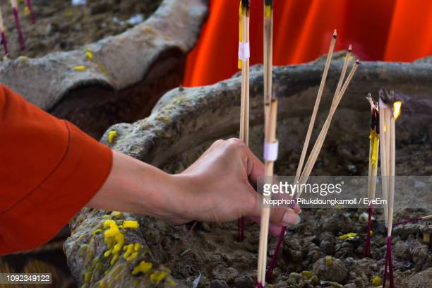 cropped hand of woman inserting burning incense sticks in soil at temple - inserting stock pictures, royalty-free photos & images