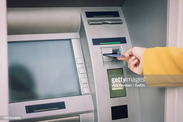 cropped hand of woman inserting card in atm machine - atm stock pictures, royalty-free photos & images