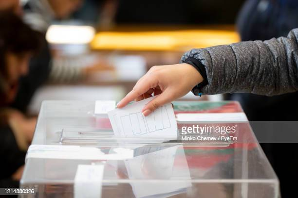 cropped hand of woman inserting papers in ballot box - ballot box stock pictures, royalty-free photos & images