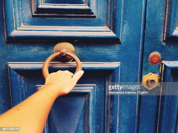 cropped hand of woman knocking door - knocking on door stock photos and pictures