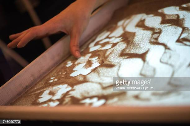 Cropped Hand Of Woman Making Sand Painting